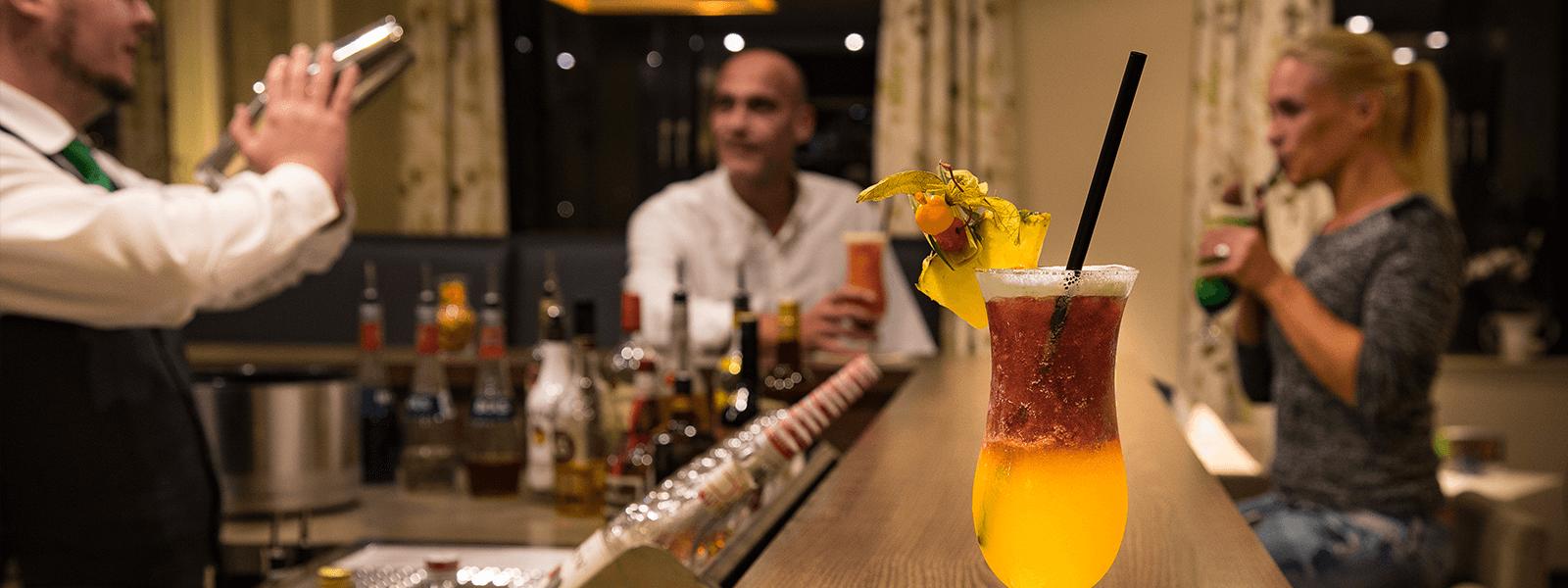 Barkeeper beim Cocktail mixen, Hotelgäste genießen an der Bartheke ihre Cocktails und auf der Theke steht ein köstlich aussehender Cocktail