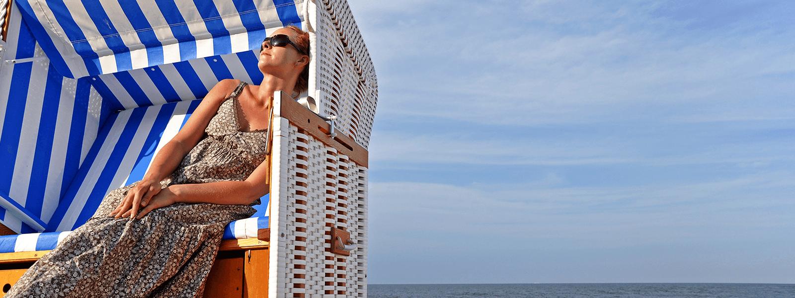 Frau sitzt im Strandkorb und genießt die Sonne