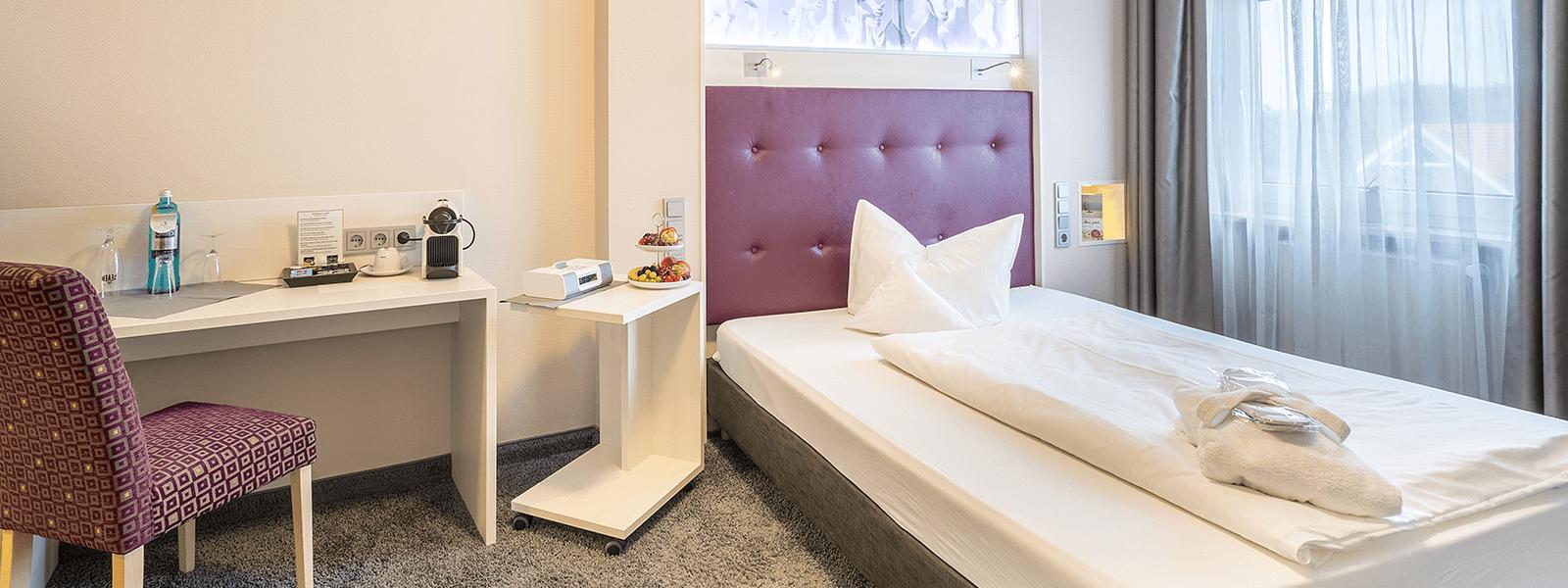 Blick ins Hotelzimmer mit Sitzgelegheit und Bett