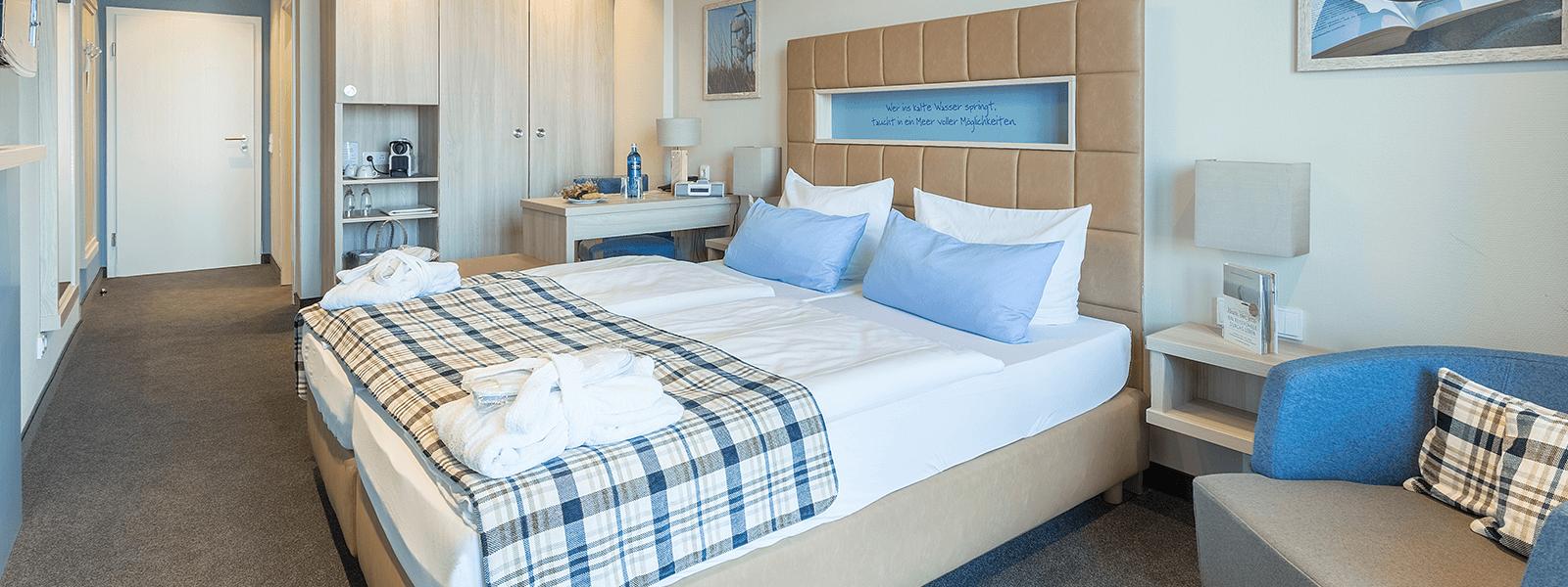 Blick ins Hotelzimmer mit Doppelbett und Sitzgelegenheit