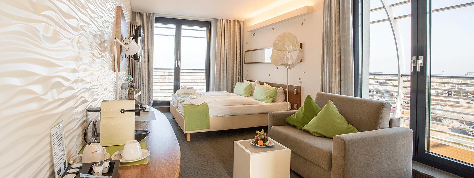 Blick ins Hotelzimmer mit Doppelbett, Couch und Balkon