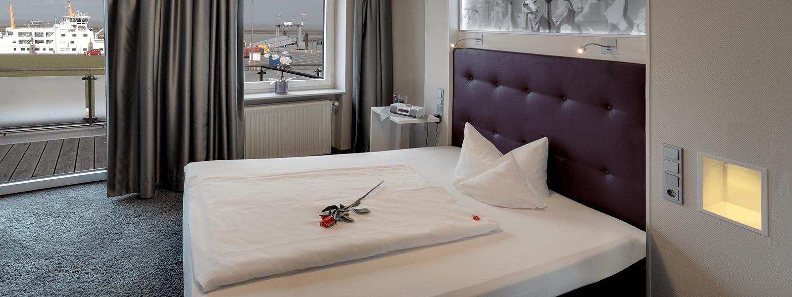 Blick ins Hotelzimmer mit King-Size Bett und Balkon