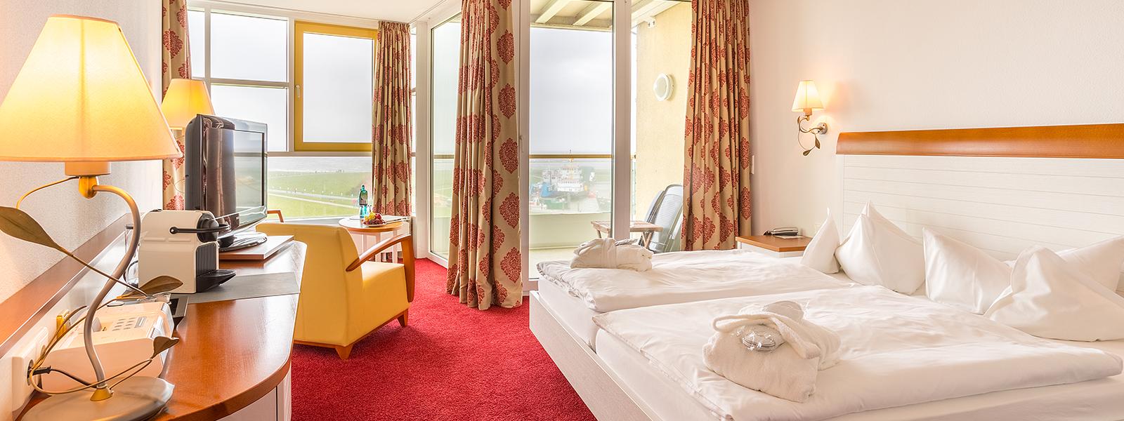 Blick ins Hotelzimmer im Westdeck mit Doppelbett und Sitzgelegenheit