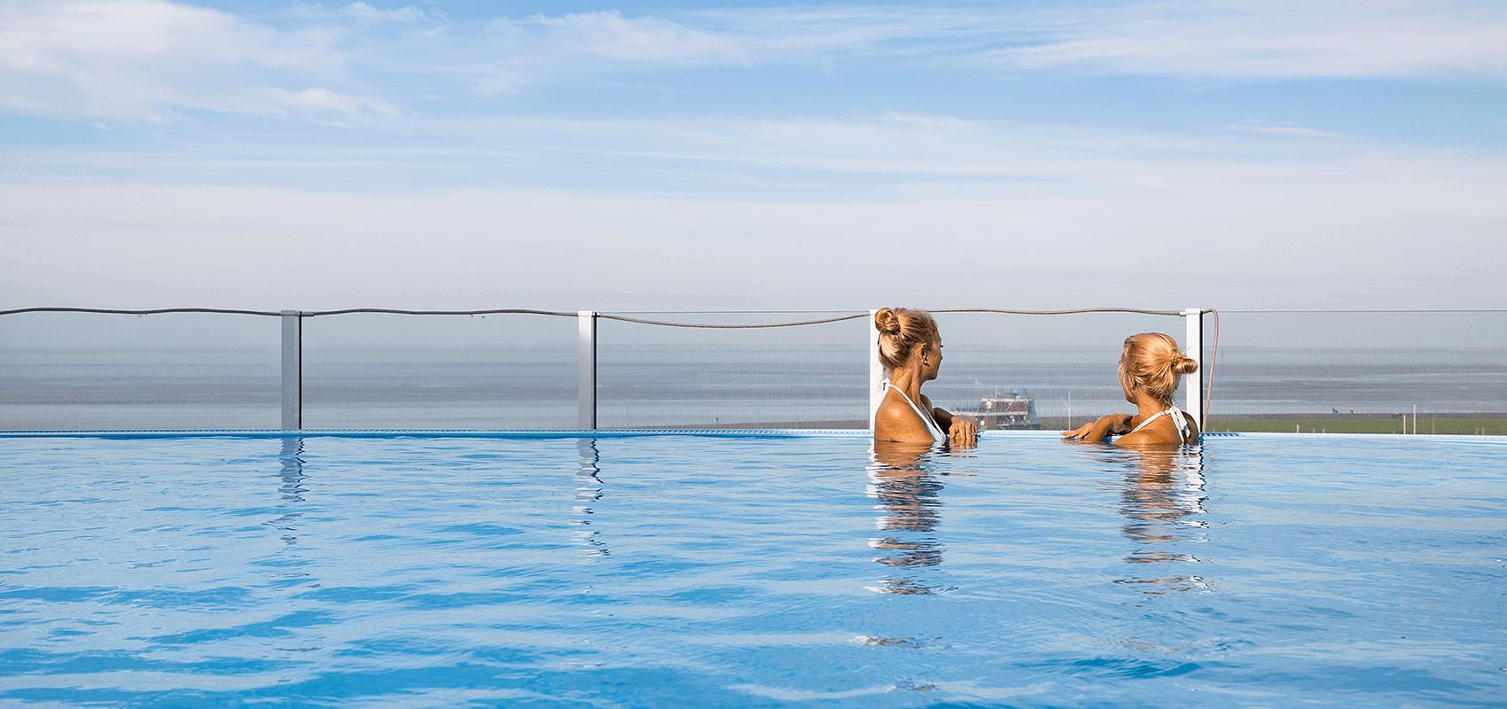 Zwei Frauen genießen den Ausblick vom Infinitypool auf dem Wellnessdeck