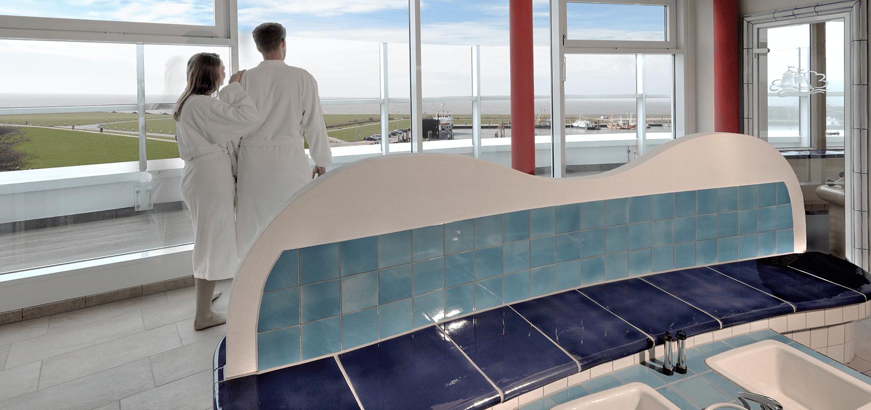 Pärchen blickt vom Wellnessdeck auf Deich, Hafen und Wattenmeer