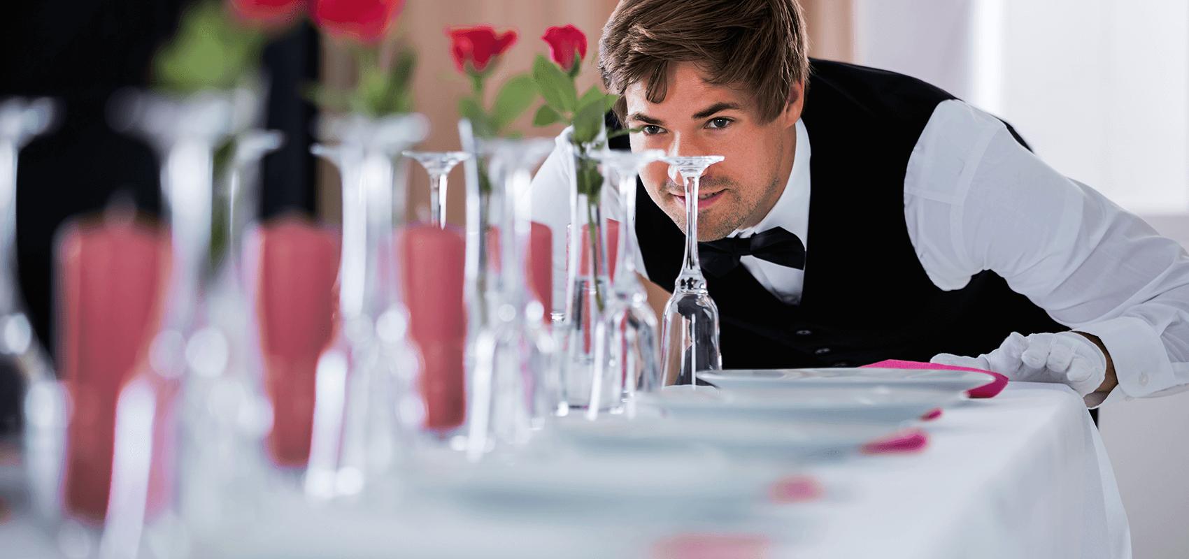 Kellner überprüft den gedeckten Tisch