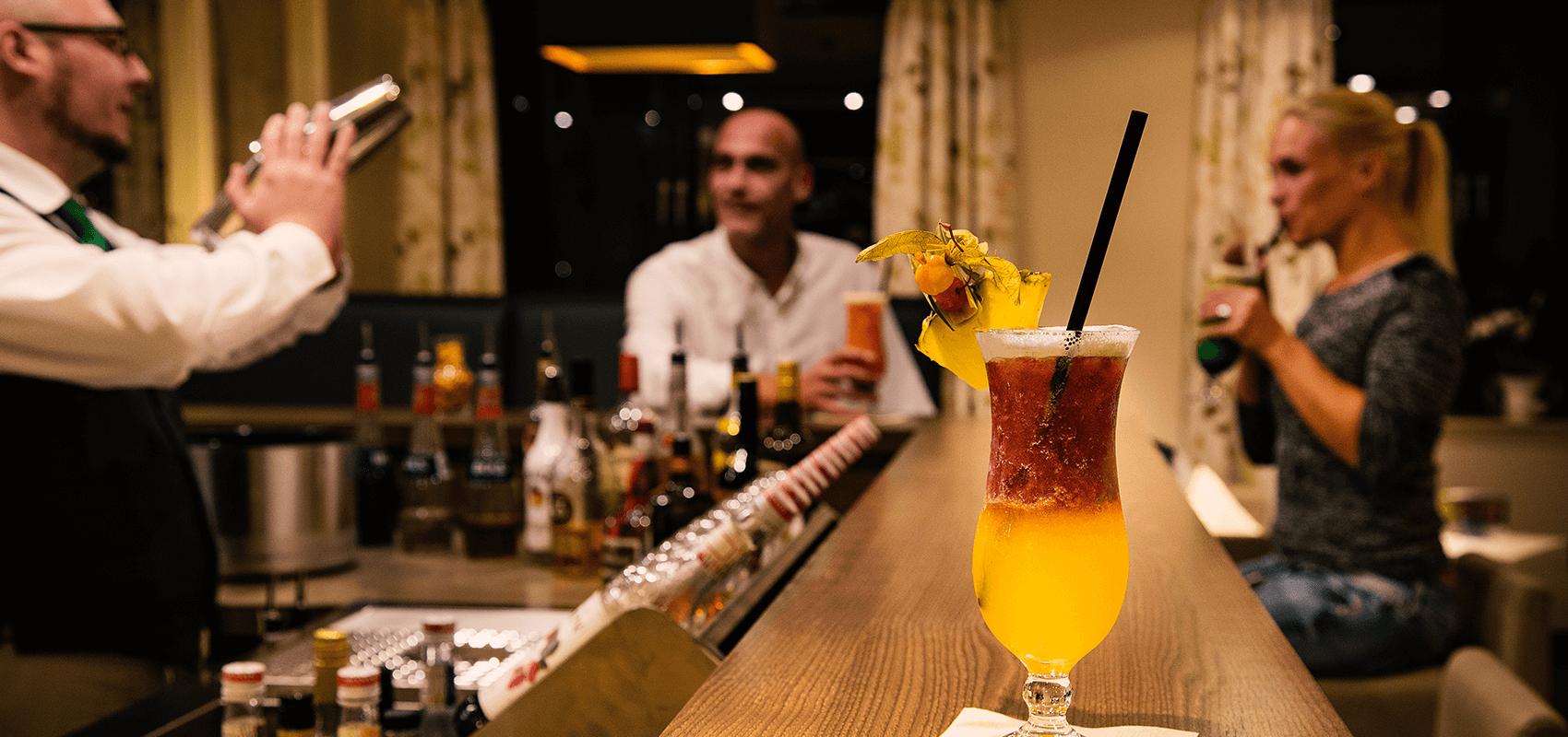 Barkeeper beim Cocktail mixen, Hotelgäste genießen an der Bar ihre Cocktails und auf der Theke steht ein köstlich aussehender Cocktail