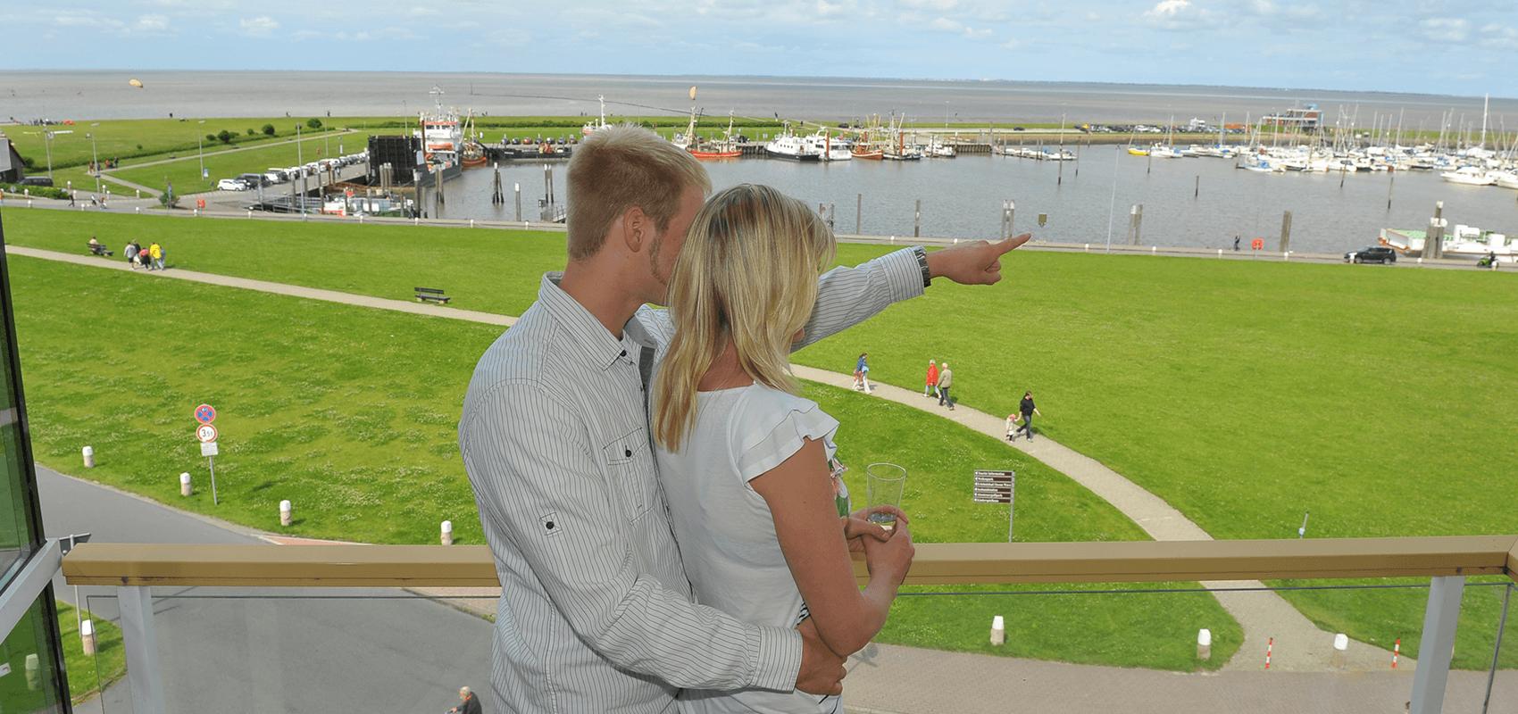 Pärchen auf dem Hotelzimmerbalkon, der Mann zeigt der Frau wo Norderney liegt