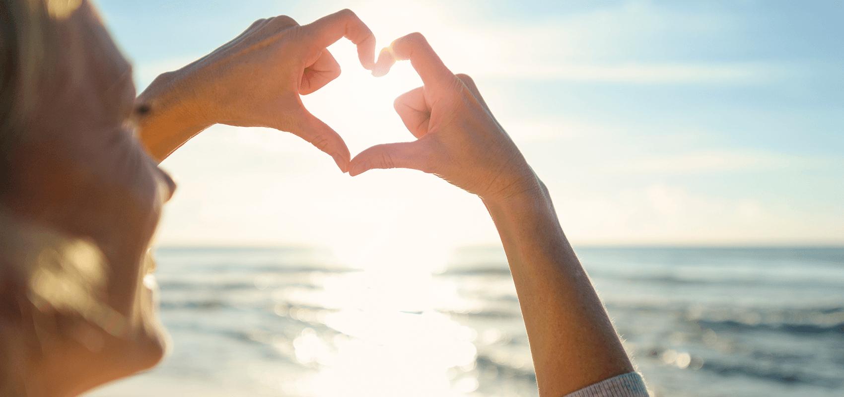 Frau formt mit ihren Fingern ein Herz, eine Liebeserklärung an die Nordsee