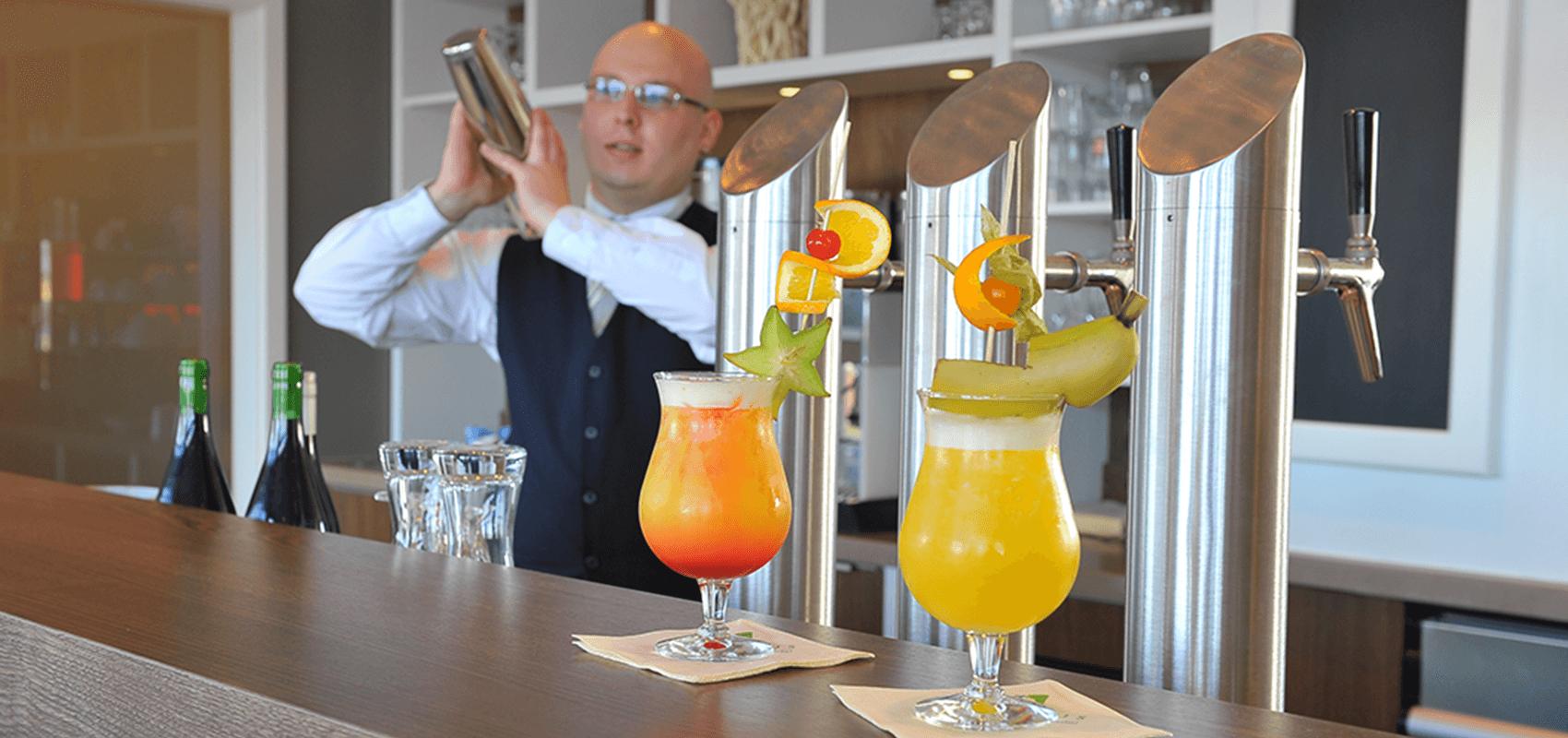 Barkeeper mixt köstliche Cocktails, zwei fertige stehen auf der Theke