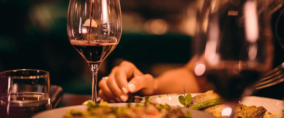 Weinglas wird mit Rotwein aufgefüllt