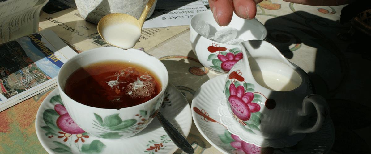 Zubereitung eines klassischen Ostfriesentees mit Sahne und Kluntje