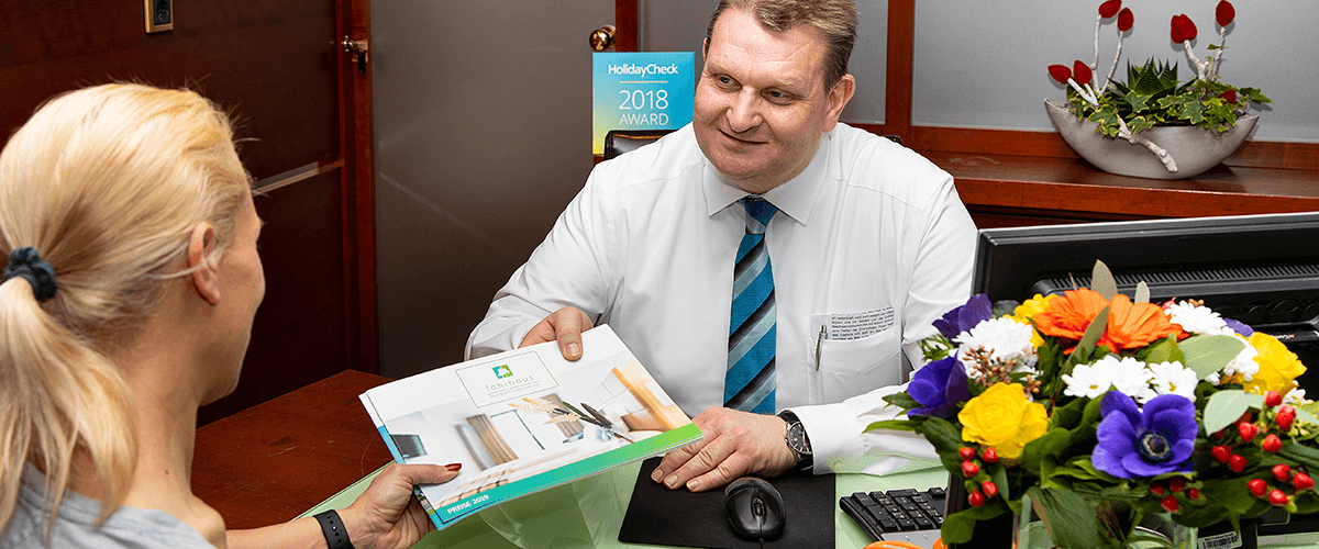 Rezeptionsmitarbeiter überreicht Hotelbroschüre an Hotelgast