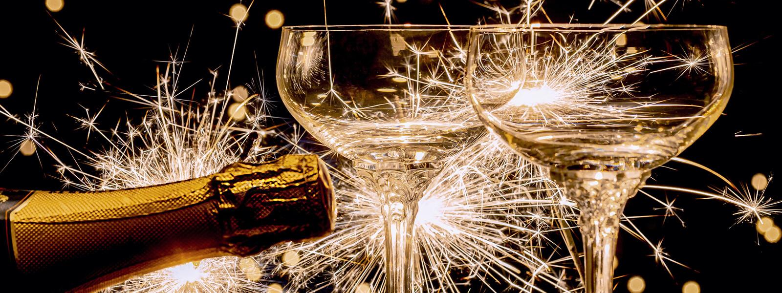 Sektflasche und Gläser im Hintergrund ein Feuerwerk